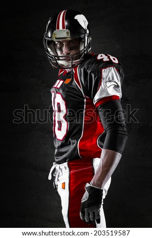 Side view of american football player on dark background - stock photo