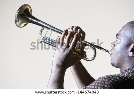 Side view of an African American man playing trumpet against gray background - stock photo
