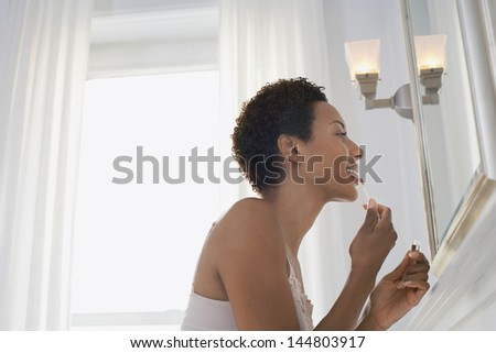 Side view of an African American woman applying lip gloss in mirror at home - stock photo