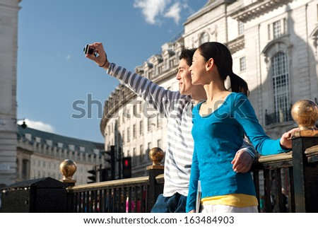 Side view of an attractive Japanese tourist couple using a consumer digital photo camera to take pictures of themselves while visiting a London landmark street during a sunny day, outdoors. - stock photo