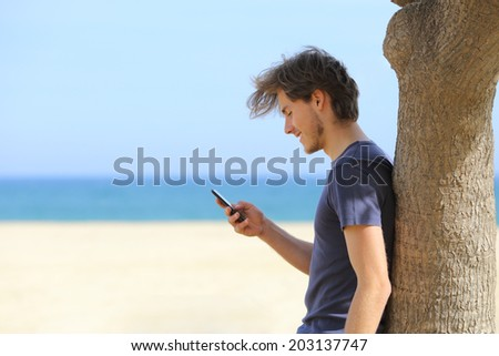 Side view of an attractive man using a smart phone on the beach with the sea and horizon in the background             - stock photo
