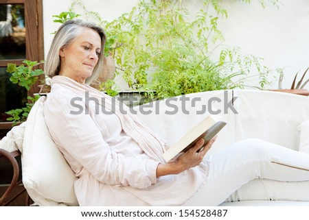 Side view of an attractive mature woman lounging and relaxing at home while reading a book and sitting on a white sofa with green plants, being tranquil and serene. - stock photo