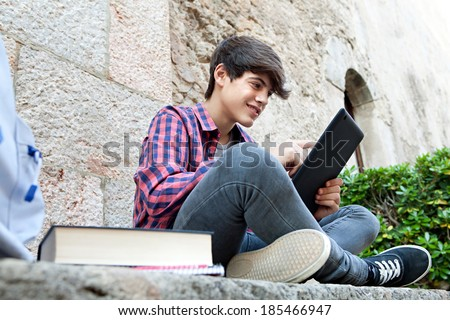 Side view of an attractive teenager boy sitting on a college campus with school books and a backpack by an old stone wall using a digital tablet pad to do his homework. Education technology lifestyle. - stock photo