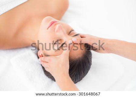 Side view of an attractive young woman receiving head massage at spa center - stock photo