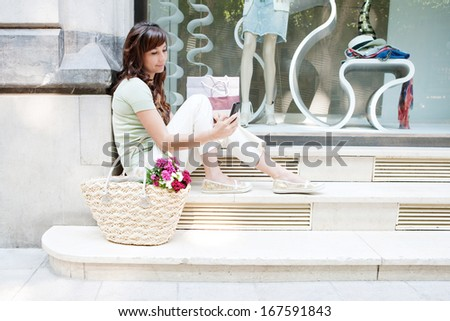 Side view of an attractive young woman sitting on the steps of a fashion store window display with manikins, holding and using her smartphone during a shopping day out, outdoors. - stock photo