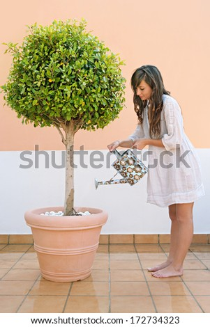 Side view of an attractive young woman watering a tree plant in a home terrace, holding a watering can and tendering her plant during a summer day. Home exterior. - stock photo