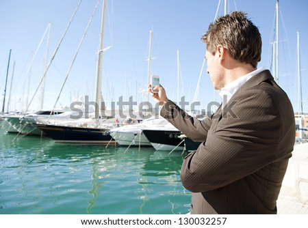 "Side view of an elegant businessman taking pictures with his ""smart phone"" on a luxurious yachts marine against a deep blue sky on a sunny day. - stock photo"