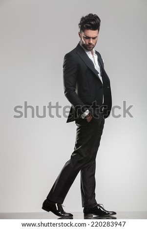 Side view of an elegant man wearing a tuxedo, walking while holding his hands in pocket, looking down. On grey background. - stock photo