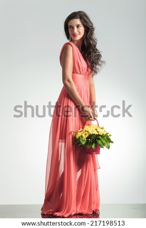side view of an elegant woman in red dress looking away while holding a flower basket in studio - stock photo