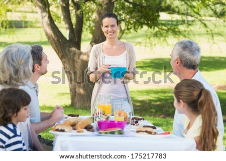 Side view of an extended family having lunch in the lawn - stock photo
