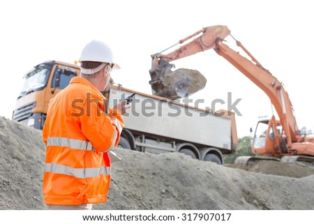 Side view of architect using walkie-talkie while working at construction site - stock photo