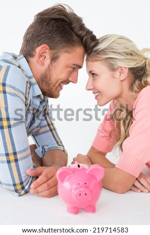 Side view of attractive young couple with piggybank over white background - stock photo