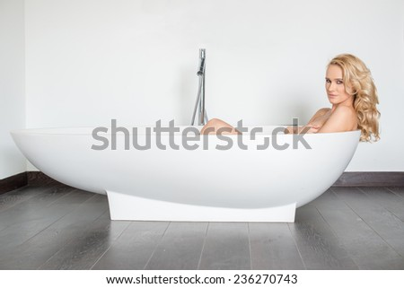 Side View of Beautiful Blond Woman Looking at Camera and Relaxing in Modern Bathtub - stock photo
