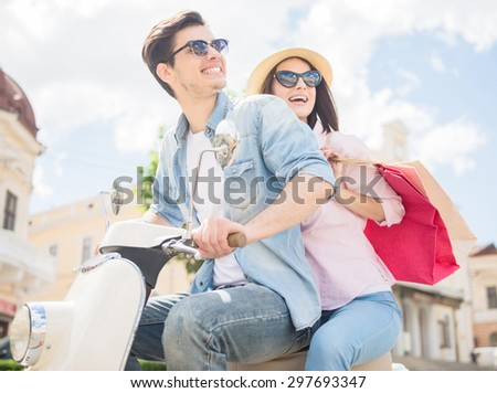Side view of beautiful young couple riding scooter, happy woman holding bags. Shopping together. - stock photo