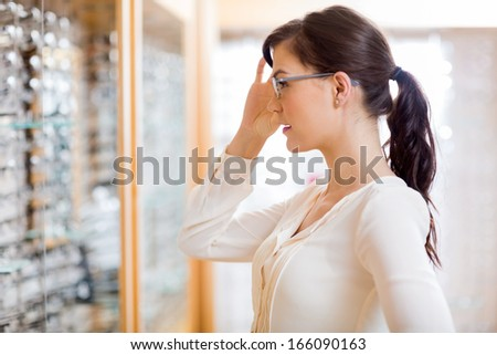 Side view of beautiful young woman trying new glasses at optician store - stock photo