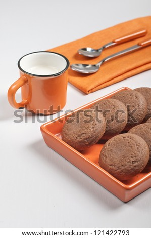 Side view of biscuits in orange ceramic pan, spoons on napkin and cup of milk on white wooden background - stock photo