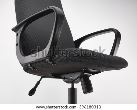 Side view of black office swivel chair on wheels with a mechanism for adjusting the height. On white background. - stock photo
