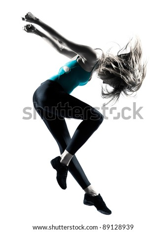 Side view of blond haired woman doing gymnastic jump in studio on white background - stock photo