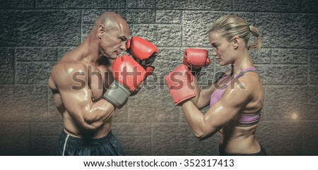 Side view of boxers with fighting stance against grey brick wall - stock photo