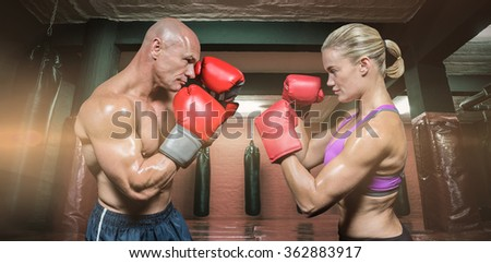 Side view of boxers with fighting stance against red boxing area with punching bags - stock photo