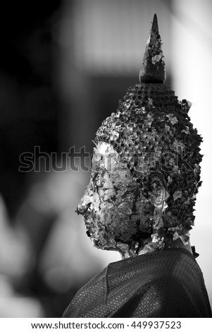 Side view of Buddha statue in black and white shot. - stock photo