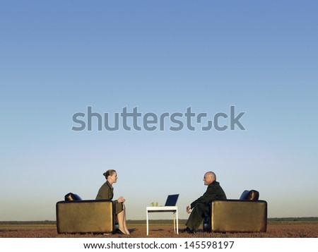 Side view of business people on armchairs communicating on field - stock photo