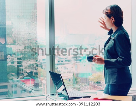 Side view of Business woman looking out the window with coffee cup in hand - stock photo