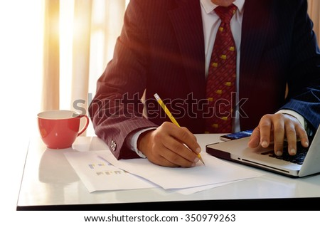 Side view of Businessman analysis charts on the paper reported in office. - stock photo