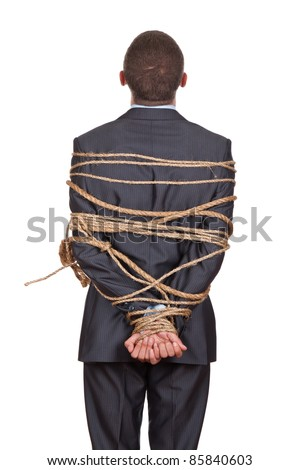 Side view of businessman executive tied up with rope, looking up standing back - stock photo