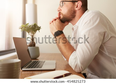 Side view of businessman sitting at his desk with a laptop and looking away. Man at his workdesk thinking of business solutions. - stock photo