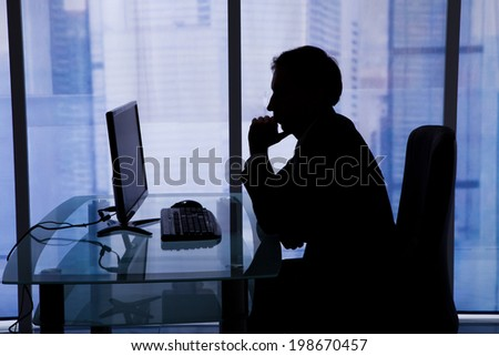 Side view of businessman using computer in office - stock photo