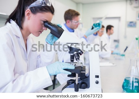 Side view of busy group of researchers working on experiments in the laboratory - stock photo