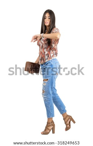 Side view of casual woman walking and checking time on hand watch. Full body length portrait isolated over white studio background. - stock photo