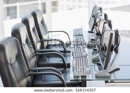 Side view of chairs, computers and headset in a modern office or training center - stock photo