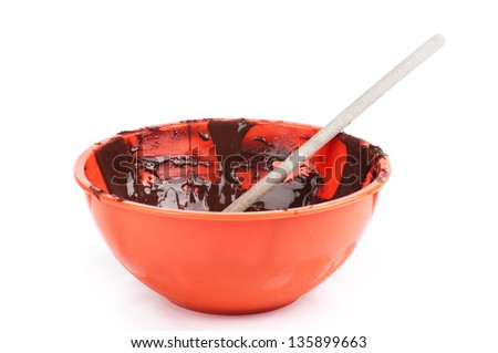 Side View of Chocolate Frosting in Orange Bowl on white background - stock photo