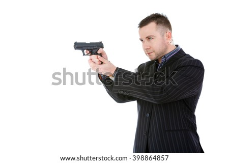 Side view of closeup portrait of a classy businessman or mobster or security guard holding a gun isolated over a white background - stock photo