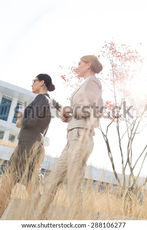 Side view of confident businesswomen walking against clear sky - stock photo