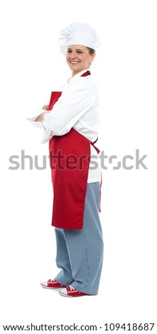 Side view of confident middle aged female chef posing with arms crossed looking at you - stock photo