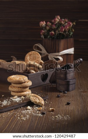 Side view of cookies in the box and dry roses on wooden board. Biscuits stack and one broken cookie with crumbs on cutting board. - stock photo