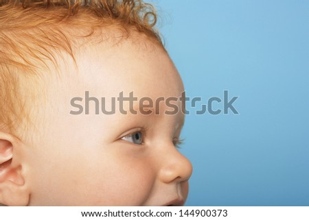 Side view of cute baby boy looking away on blue background - stock photo