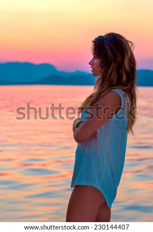Side view of cute girl enjoying beautiful red and yellow sunset over sea, spending evening on the beach, freedom and enjoyment concept - stock photo