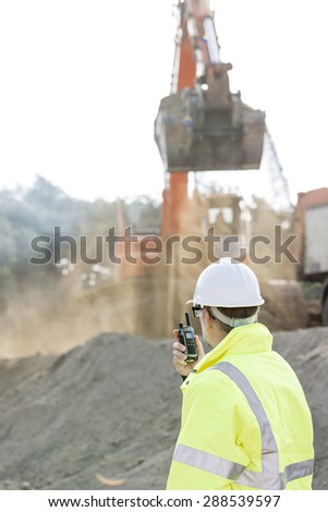 Side view of engineer using walkie-talkie at construction site - stock photo