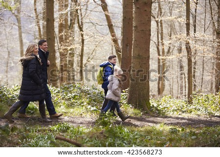 Side view of family walking in a wood - stock photo