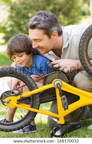 Side view of father and son fixing bike - stock photo