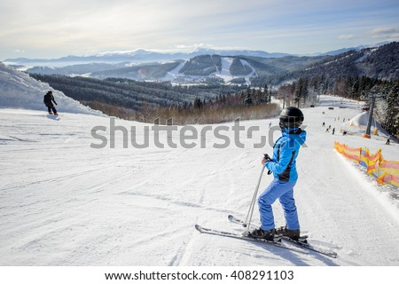 Side view of female skier resting on the middle of ski slope against ski lift and beautiful winter landscape background on a sunny day. Ski resort. Winter sports concept. - stock photo