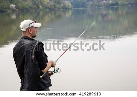 Side View Of Fisherman Reeling String And Throwing Rod In The Calm Lake, Half-Length Shot - stock photo