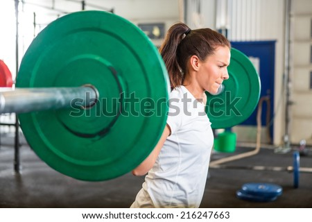 Side view of fit young woman lifting barbell in fitness box - stock photo
