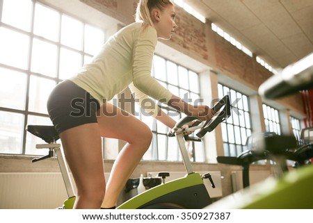 Side view of focused young woman exercising on bike in health club. Fitness female workout on bicycle in gym. - stock photo