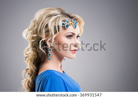 Side view of gorgeous girl wearing sapphire accessories over grey background. - stock photo