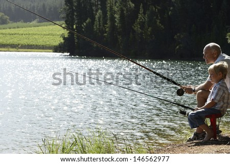 Side view of grandfather and grandson fishing together by lake - stock photo